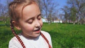 Χαριτωμένο λουλούδι πικραλίδων μικρών κοριτσιών φυσώντας υπαίθρια Το ευτυχές παιδί που έχει τη διασκέδαση σταθμεύει την άνοιξη απόθεμα βίντεο