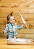 Χαριτωμένο μαγείρεμα παιδιών με τη ζύμη, το αλεύρι και την ξύλινη κυλώντας καρφίτσα Στοκ Φωτογραφία
