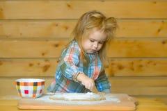 Χαριτωμένο μαγείρεμα παιδιών με τη ζύμη, το αλεύρι και το κύπελλο στο ξύλο Στοκ Εικόνες