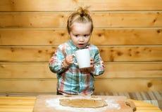 Χαριτωμένο μαγείρεμα παιδιών με τη ζύμη, το αλεύρι και το φλυτζάνι στο ξύλο Στοκ Εικόνες