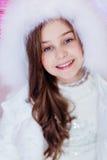 Χαριτωμένο μακρυμάλλες νέο κορίτσι με τα μπλε μάτια σε μια άσπρη κουκούλα με Στοκ Φωτογραφία