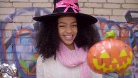 Χαριτωμένο μαύρο κορίτσι εφήβων στο καπέλο μαγισσών που θέτει τα πρόσωπα σε αποκριές απόθεμα βίντεο