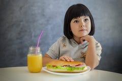 Χαριτωμένο μαύρο μικρό κορίτσι τρίχας που έχει το πρόγευμα και που πίνει το πορτοκάλι Στοκ εικόνα με δικαίωμα ελεύθερης χρήσης