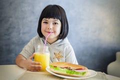Χαριτωμένο μαύρο μικρό κορίτσι τρίχας που πίνει το χυμό από πορτοκάλι και που τρώει το SAN Στοκ εικόνες με δικαίωμα ελεύθερης χρήσης