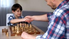 Χαριτωμένο μεγαλοφυίας παιχνίδι σκακιού παιδιών κερδίζοντας, χειραψία με τον υπερήφανο πατέρα του, χόμπι στοκ εικόνες