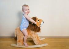 Χαριτωμένο μικρό αγοράκι που οδηγά στο παιχνίδι λιονταριών Ευτυχείς συγκινήσεις παιδιών Στοκ Φωτογραφίες