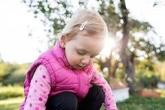 Χαριτωμένο μικρό κορίτσι έξω στη φύση μια ηλιόλουστη ημέρα Στοκ Εικόνες