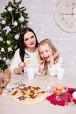 Χαριτωμένο μικρό κορίτσι και η μητέρα της που μαγειρεύουν και που τρώνε το γουργούρισμα Χριστουγέννων στοκ εικόνες με δικαίωμα ελεύθερης χρήσης