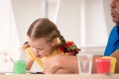 Χαριτωμένο μικρό κορίτσι και ο πατέρας της που χρωματίζουν από κοινού Στοκ Εικόνες