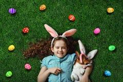 Χαριτωμένο μικρό κορίτσι και το σκυλί της με τα αυτιά κουνελιών που βρίσκονται στο πράσινο gra στοκ φωτογραφία με δικαίωμα ελεύθερης χρήσης
