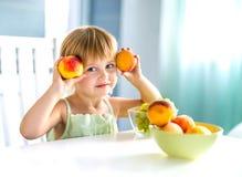 Χαριτωμένο μικρό κορίτσι με τα ροδάκινα στα χέρια στον πίνακα Στοκ Εικόνες