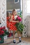 Χαριτωμένο μικρό κορίτσι με τα peonies στο στούντιο μπροστά από τον καθρέφτη στοκ εικόνες