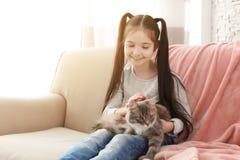 Χαριτωμένο μικρό κορίτσι με τη συνεδρίαση γατών στον καναπέ Στοκ Εικόνες