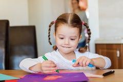 Χαριτωμένο μικρό κορίτσι με τις πλεξούδες που επισύρει την προσοχή σε ζωηρόχρωμα χαρτιά Στοκ φωτογραφία με δικαίωμα ελεύθερης χρήσης