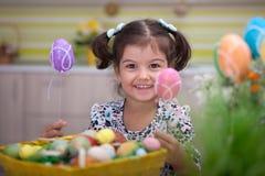 Χαριτωμένο μικρό κορίτσι με το σύνολο καλαθιών των ζωηρόχρωμων αυγών Πάσχας Στοκ εικόνες με δικαίωμα ελεύθερης χρήσης