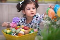 Χαριτωμένο μικρό κορίτσι με το σύνολο καλαθιών των ζωηρόχρωμων αυγών Πάσχας Στοκ Εικόνες
