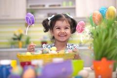 Χαριτωμένο μικρό κορίτσι με το σύνολο καλαθιών των ζωηρόχρωμων αυγών Πάσχας Στοκ Εικόνα