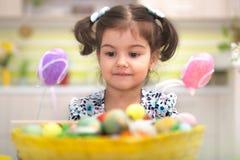 Χαριτωμένο μικρό κορίτσι με το σύνολο καλαθιών των ζωηρόχρωμων αυγών Πάσχας Στοκ Φωτογραφία