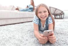 Χαριτωμένο μικρό κορίτσι με το smartphone που βρίσκεται στον τάπητα στο καθιστικό στοκ φωτογραφίες με δικαίωμα ελεύθερης χρήσης