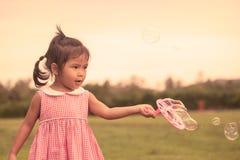 Χαριτωμένο μικρό κορίτσι παιδιών που έχει τη διασκέδαση που παίζει με το παιχνίδι φυσαλίδων της Στοκ Φωτογραφία