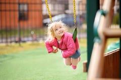 Χαριτωμένο μικρό κορίτσι που έχει τη διασκέδαση στην υπαίθρια παιδική χαρά Στοκ εικόνα με δικαίωμα ελεύθερης χρήσης