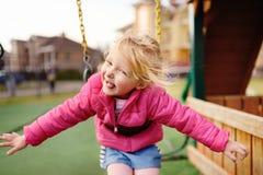 Χαριτωμένο μικρό κορίτσι που έχει τη διασκέδαση στην υπαίθρια παιδική χαρά Στοκ Φωτογραφίες