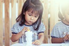 Χαριτωμένο μικρό κορίτσι που έχει τη διασκέδαση για να χρωματίσει στην κούκλα στόκων Στοκ Φωτογραφία
