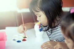 Χαριτωμένο μικρό κορίτσι που έχει τη διασκέδαση για να χρωματίσει στην κούκλα στόκων Στοκ φωτογραφία με δικαίωμα ελεύθερης χρήσης