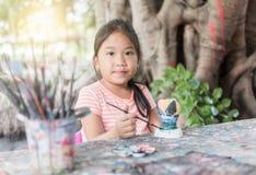 Χαριτωμένο μικρό κορίτσι που έχει τη διασκέδαση για να χρωματίσει στην κούκλα στόκων στοκ εικόνα με δικαίωμα ελεύθερης χρήσης