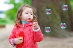 Χαριτωμένο μικρό κορίτσι που έχει τη διασκέδαση με τις φυσαλίδες σαπουνιών Στοκ εικόνες με δικαίωμα ελεύθερης χρήσης