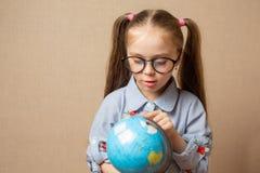 Χαριτωμένο μικρό κορίτσι που αγκαλιάζει τη σφαίρα γη έννοιας που απομονώνεται εκτός από το λευκό στοκ εικόνες