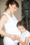 Χαριτωμένο μικρό κορίτσι που αγκαλιάζει την κοιλιά μητέρων της Στοκ φωτογραφίες με δικαίωμα ελεύθερης χρήσης