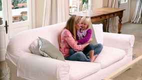 Χαριτωμένο μικρό κορίτσι που αγκαλιάζει τη μητέρα της στον καναπέ απόθεμα βίντεο