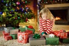 Χαριτωμένο μικρό κορίτσι που αισθάνεται δυστυχισμένο με τα δώρα Χριστουγέννων της Συνεδρίαση παιδιών από μια εστία σε ένα άνετο σ στοκ εικόνες