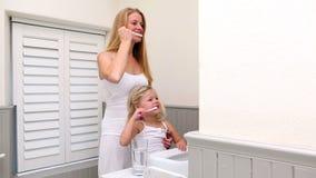 Χαριτωμένο μικρό κορίτσι που βουρτσίζει τα δόντια της με τη μητέρα της απόθεμα βίντεο