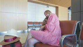 Χαριτωμένο μικρό κορίτσι που βρίσκεται στην περιτύλιξη μητέρων της ` s στη αίθουσα αναμονής στον αερολιμένα απόθεμα βίντεο