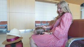 Χαριτωμένο μικρό κορίτσι που βρίσκεται στην περιτύλιξη μητέρων της ` s στη αίθουσα αναμονής στον αερολιμένα φιλμ μικρού μήκους