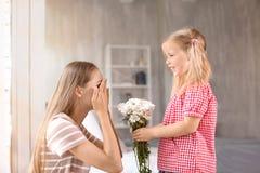 Χαριτωμένο μικρό κορίτσι που δίνει τα λουλούδια στη μητέρα της στο σπίτι στοκ φωτογραφίες με δικαίωμα ελεύθερης χρήσης