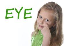 Χαριτωμένο μικρό κορίτσι που δείχνει το μάτι της στα μέλη του σώματος που μαθαίνουν τις αγγλικές λέξεις στο σχολείο Στοκ Φωτογραφίες