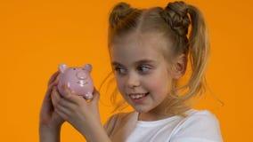 Χαριτωμένο μικρό κορίτσι που η piggy τράπεζα με τα νομίσματα και που χαμογελά, προσωπική αποταμίευση απόθεμα βίντεο