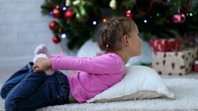Χαριτωμένο μικρό κορίτσι που κάνει την άσκηση γιόγκας στο πάτωμα δίπλα στο χριστουγεννιάτικο δέντρο απόθεμα βίντεο