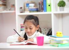 Χαριτωμένο μικρό κορίτσι που κάνει την εργασία που διαβάζει τις χρωματίζοντας σελίδες βιβλίων wr Στοκ φωτογραφία με δικαίωμα ελεύθερης χρήσης