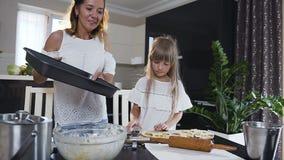 Χαριτωμένο μικρό κορίτσι που κατασκευάζει τα μπισκότα από την ακατέργαστη ζύμη υπό μορφή καρδιών και αστεριών Η όμορφη γυναίκα βά φιλμ μικρού μήκους
