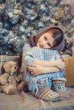 Χαριτωμένο μικρό κορίτσι που καλύπτεται στο θερμό μαντίλι που περιμένει τα Χριστούγεννα στοκ εικόνα