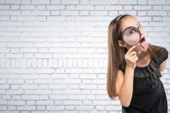 Χαριτωμένο μικρό κορίτσι που κοιτάζει μέσω μιας ενίσχυσης - άσπρο υπόβαθρο τουβλότοιχος γυαλιού έννοια εκπαιδευτική στοκ εικόνες
