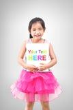 Χαριτωμένο μικρό κορίτσι που κρατά το λευκό πίνακα απομονωμένο στο γκρίζο υπόβαθρο Στοκ Εικόνες