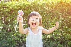 Χαριτωμένο μικρό κορίτσι που κρατά το lollipop στην ισοτιμία Στοκ φωτογραφία με δικαίωμα ελεύθερης χρήσης