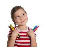 Χαριτωμένο μικρό κορίτσι που κρατούν τα ζωηρόχρωμους μολύβια και τους δείκτες το u Στοκ Φωτογραφίες
