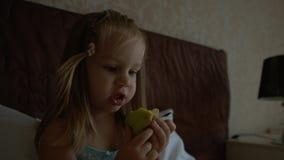 Χαριτωμένο μικρό κορίτσι που μασά το μήλο Στοκ Φωτογραφίες