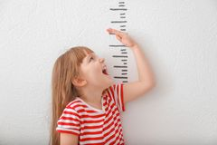 Χαριτωμένο μικρό κορίτσι που μετρά το ύψος στοκ φωτογραφίες